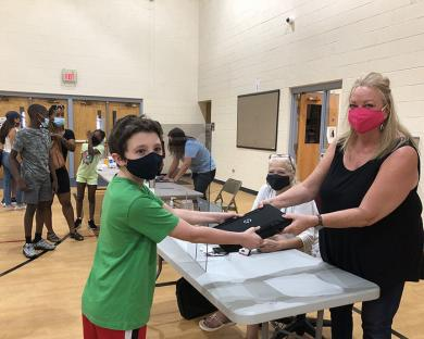 Tommy Losh, an eighth grader at James Hart School, accepts his computer device from Kristy Anderson.