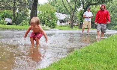 A youngster plays in a flooded street in 2014 while two adults supervise. Public works officials note that urban flooding has a range of causes and might be chronic or only occasional. This section of Olive Road rarely floods, so the cause might have been a blocked storm sewer grate. (Chronicle file photo)