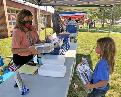Violet Gruberman needs her second grade teacher Michelle Klupchak during supply distribution day at Willow School.