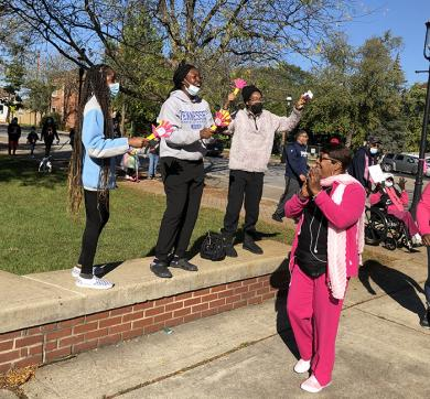 Members of the Key Club at Homewood-Flossmoor High School were the welcoming team as walkers reached Irwin Park. Walker Dorothy Johnson gives a round of applause to three of the volunteers, from left, Kendahl McCall, Nyla McGowan and Alyssa Ford. (MT)