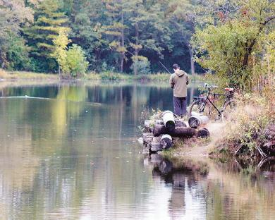 A bicycling fisherman tries his luck on a calm lake in Izaak Walton Nature Preserve.