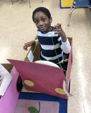Odina Muodeme holds up the key for his box car. Kindergarteners each made a key for their car that was equipped with a steering wheel, odometer and side mirror.