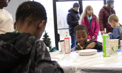 From left, Broderick and Braylon Booth work on their cookie decorations at Coldwell Banker during Winterfest.