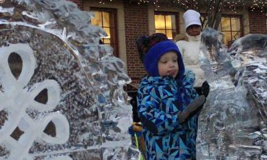 Miles Tanner, 2, poses for a photo with the Winterfest ice sculptures.