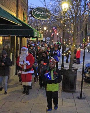 Santa Claus leads the parade of carolers south on Sterling Avenue on their way to Park Place for the menorah and Christmas tree lighting ceremony.