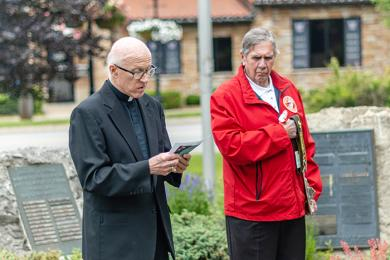 John Beele listens as Father Dan Jarosewic, left, opens the Homewood ceremony with a prayer. (ABS)
