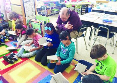 One of the many unofficial duties District 153 Superintendent Dale Mitchell took on during his 27 years with the district was visiting the schools. He read with second graders at Willow School in 2019. Mitchell is retiring in June.  (Chronicle file photo)