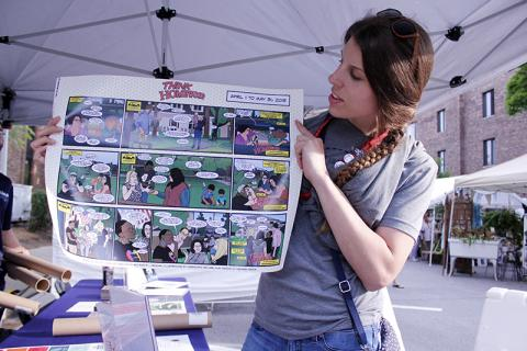 Sarah Meeker, assistant events coordinator for the village, shows a poster version of the Think Homewood comic strips.