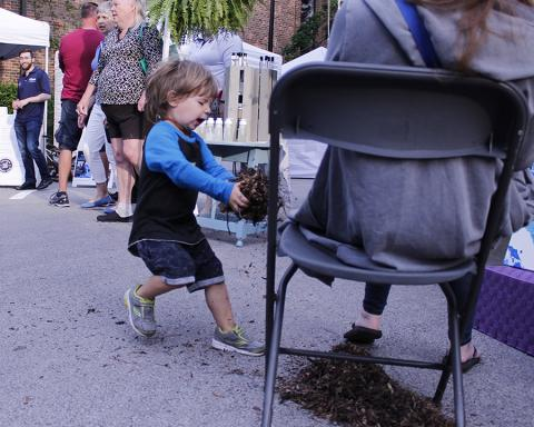There were lots of kids activities at the fair, but young Mason Fletcher came up with his own, methodically piling dirt and leaves under his mother's chair. She thought perhaps he was creating an ant farm.