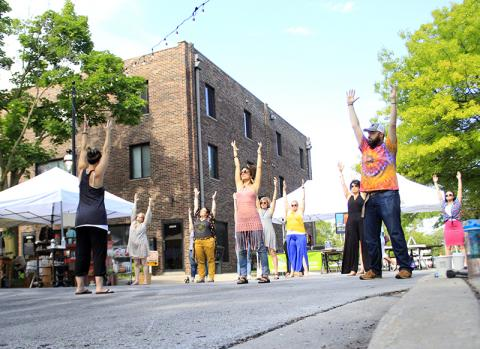 The yoga begins before the fair opens as Liz Smith leads vendors in stretching exercises.