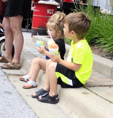 Two youngsters enjoy sno-cones at the Artisan Street Fair.