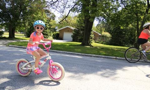 Ava Monroe pedals south on Braeburn Avenue during the Bike the Gem event July 13.