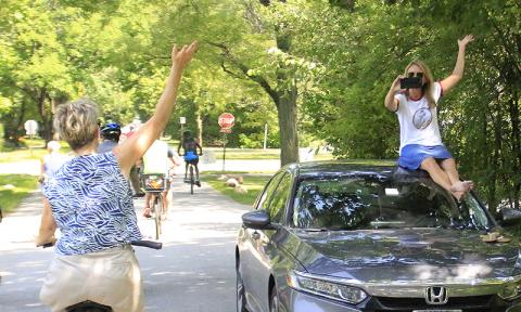 Cyclist Patty Houlihan, left, greets Katie Sullivan, who is getting video of the ride from the top of her car.