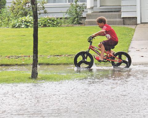 A youngster bikes through a flooded sidewalk along Olive Road in Homewood in 2014. Most flooding in Homewood and Flossmoor is due to storm water drainage rather than stream overflow. (Chronicle file photo)