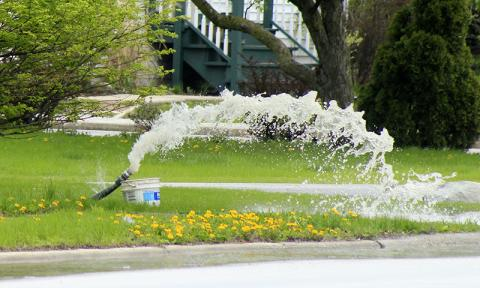 A wet May contributed to local flooding. This resident resorted to a pump to bring water to the street, where the water could find its way to the storm sewer system. (Chronicle file photo)
