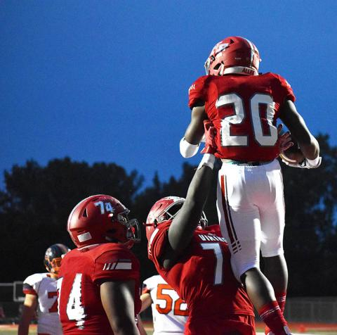 Kelden McCall, No. 77, lifts up running back Sean Allen as they celebrate a touchdown during the Vikings' homecoming game on Friday.
