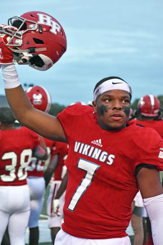 Kellen Williams lifts his helmet in celebration during the H-F High homecoming football game.