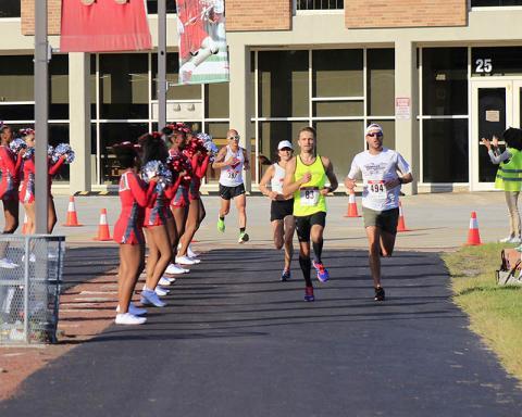 Cheer teams greet runners as the course cuts through the Homewood-Flossmoor High School campus.