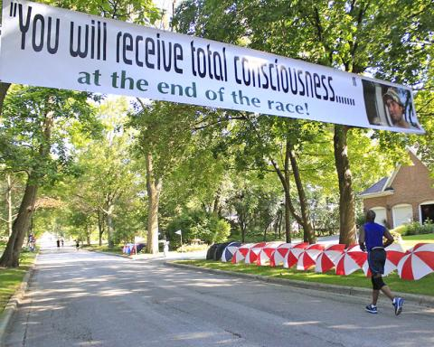"""Borrowing a line from the movie """"Caddyshack,"""" a banner on Brassie Avenue reads, """"You will receive total consciousness ... at the end of the race!"""""""