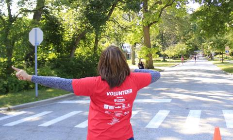 One of the many volunteer race marshals directs runners at the intersection of Brassie Avenue and Flossmoor Road.