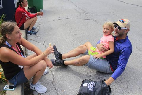Rachel Lewis, left, rests with her husband, James, and daughter, Vivian, after finishing her first distance race.