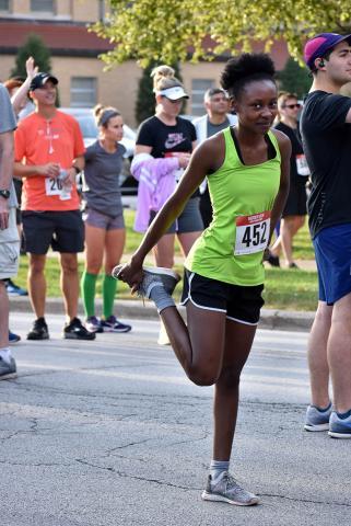 Stretching her legs before running in the Hidden Gem Half Marathon in Flossmoor is Imani Fountain of Olympia Fields.