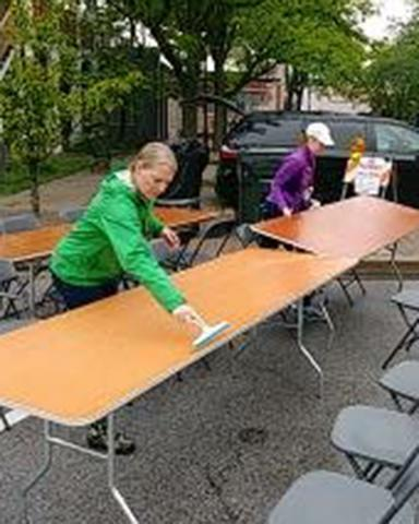 Homewood Marketing Director Jennifer Quirke, left, and Events Manager Allisa Opyd brush water from tables early Saturday.