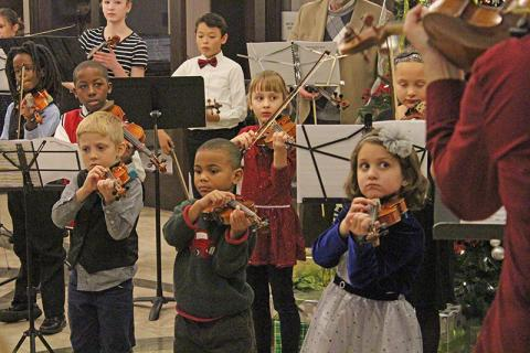 Local Suzuki strings students perform in the lobby of La Banque Hotel.