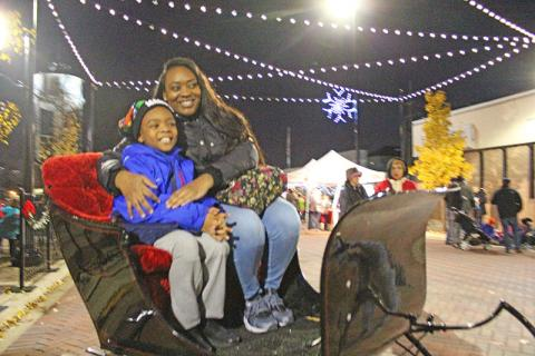 Tre Smith and his mom, Alesha Palmer, try out Santa's sleight on Martin Square.