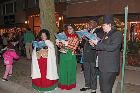 A group of carolers in vintage garb sing in front of Homewood Florists on Martin Avenue.