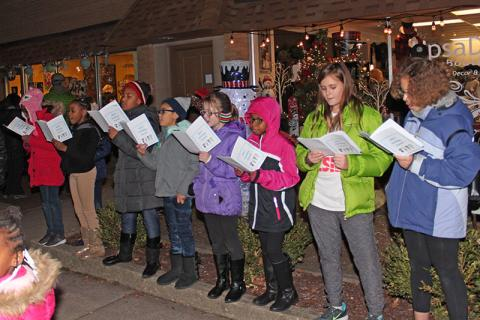 Girl Scout troop 20261 sings in front of Be Free Juice Bar on Martin Avenue.