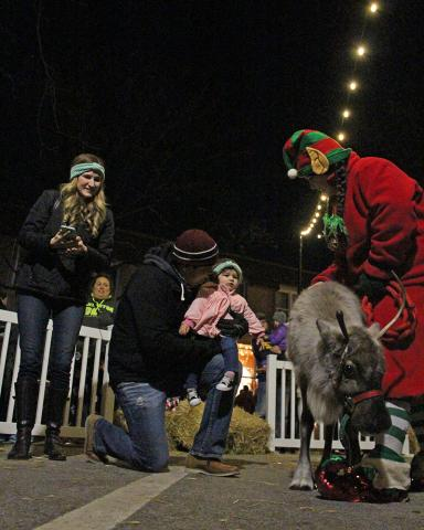 Louisa Chavez, 1, prepares to touch a reindeer with help from her father, Daniel, while her mother, Sarah, looks on.