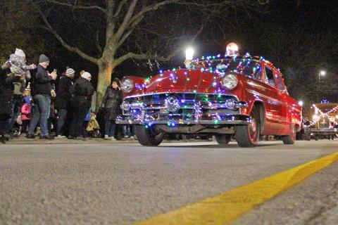 Local historian Jim Wright leads the parade of decorated vintage cars.