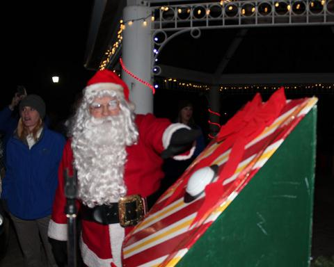 Santa Claus hits the big button that turns on the lights of the community Christmas tree in Irwin Park.