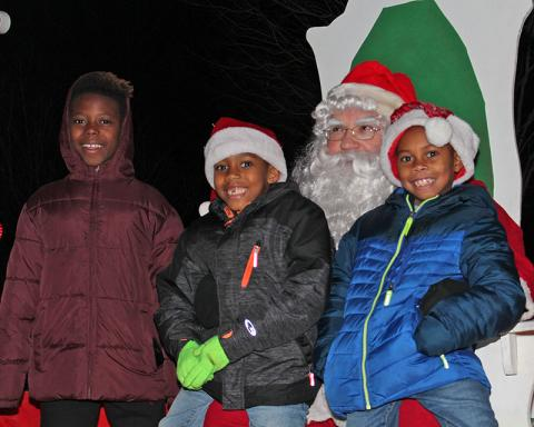 The first youngsters to sit in Santa's lap after the tree lighting are, from left, Leremiah, Jordan and Rashaun Davis of Homewood.