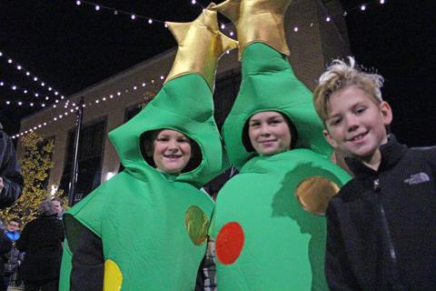 """From left, Jack Ermshler, Ben Foro (dressed as Christmas trees) and Quinn Michel. The three regaled festival goers with a spiel reminding them to recycle: """"Merry Christmas. Don't forget to recycle your tree at Irons Oaks."""""""