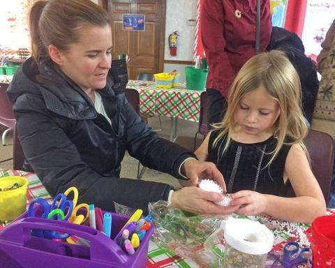 Michelle Nelson of Flossmoor helps her daughter, Kammi, 7, create a snow craft at the Homewood Science Center as part of the Holiday Lights festivities. (Photo by Marilyn Thomas)
